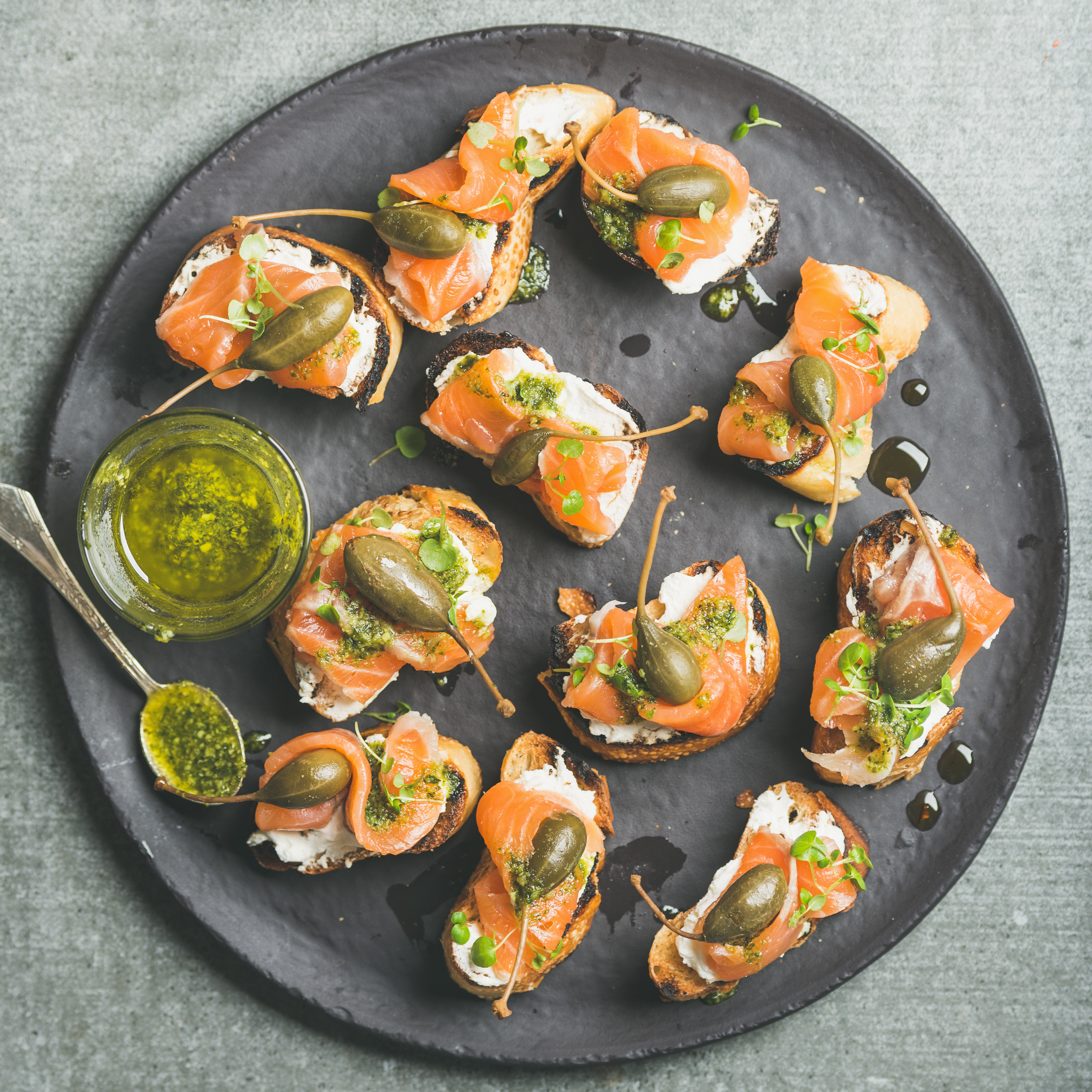 Homemade salmon crostini with cream-cheese, watercress, capers and pesto suace in round black slate stone plate over grey background, top view, square crop